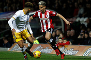 Sergi Canos of Brentford (R) takes on Liam Palmer of Sheffield Wednesday (L). EFL Skybet football league championship match, Brentford v Sheffield Wednesday at Griffin Park in London on Saturday 30th December 2017.<br /> pic by Steffan Bowen, Andrew Orchard sports photography.