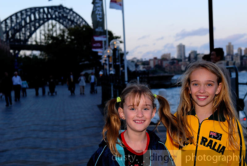 Sisters (6 years old, 10 years old) at Circular Quay at sunset, with Sydney Harbour Bridge in background. Circular Quay, Sydney, Australia