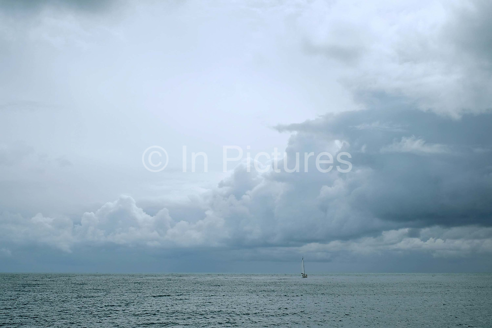 A lone yacht at sea during stormy weather in Brixham, Devon, United Kingdom on 25 July 2017