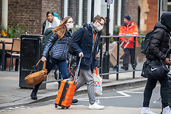 © Licensed to London News Pictures. 19/03/2020. London, UK. Travellers in masks with suitcases and rucksacks at London Victoria Bus Station as London prepares to shutdown over the Coronavirus pandemic crisis. Photo credit: Alex Lentati/LNP