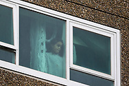 A young girl inside the Sutton Street housing complex looks out to the outside world as she is prohibited from leaving her home amid the third full day of the total lockdown of 9 housing commission high rise towers in North Melbourne and Flemington during COVID 19.After recording 191 COVID-19 cases overnight forcing Premier Daniel Andrews to announce today that all of metropolitan Melbourne along with one regional centre, Mitchell Shire will once more go back to stage three lockdowns from midnight Wednesday June 8. This comes as the residents of the housing commission towers in North Melbourne and Flemington finish their third day under extreme lockdown, despite only 27 cases being found in the towers. Members of the public gathered outside of the towers this afternoon in support of those trapped inside while riot police arrested two women for standing too close to the fence. While the women were later released, tensions are boiling over both in the towers and out. With 772 active cases in Victoria, NSW closed their border to Victoria effective at midnight tonight.