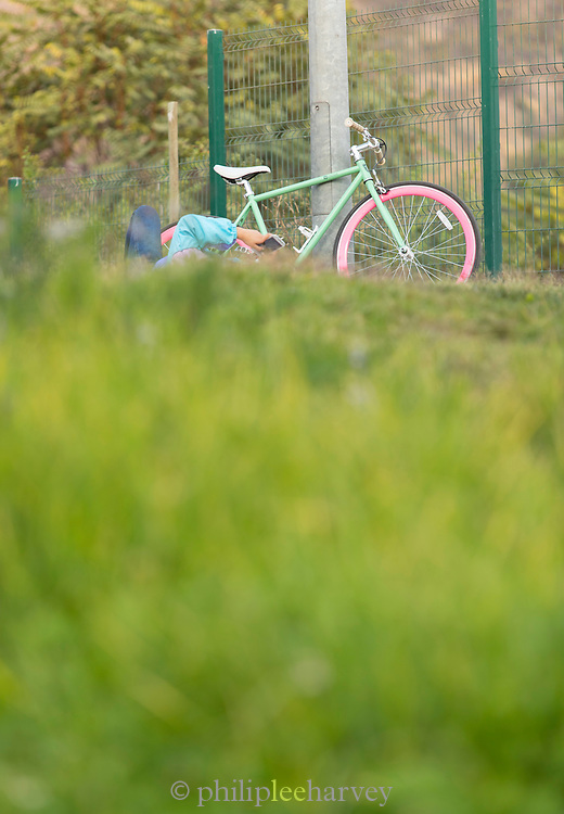 Person using mobile phone, lying near colorful bicycle, Parque Bicentenario, Santiago, Chile