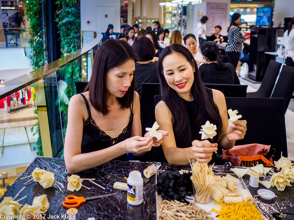 """24 MAY 2017 - BANGKOK, THAILAND: Women at the Emporium, an upscale shopping mall in Bangkok, look at the wooden roses they're making for the cremation of Bhumibol Adulyadej, the Late King of Thailand. In Thai culture it is customary to place wooden flowers in front of a deceased person's coffin or urn as a last tribute before cremation. The Royal Cremation Organisation Committee, which is overseeing plans for the cremation of Bhumibol Adulyadej, the Late King of Thailand, asked the Bangkok Metropolitan Administration (BMA) to provide three million wooden flowers for the late King's cremation. The BMA, in turn, has asked malls and civic organizations to provide flowers. The Mall Group, which owns Emporium, has pledged to provide up to one million wooden """"Wiangping"""" roses, which in Thai culture symbolize unconditional love. The late King will be cremated October 26, 2017.     PHOTO BY JACK KURTZ"""