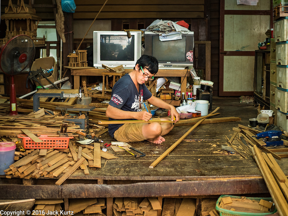 02 NOVEMBER 2016 - BANGKOK, THAILAND:  KO, Gob's brother, meaures teak for a spirit house. He works with his sister in the small family owned workshop that makes spirit houses by hand out of teak wood in the Ban Fuen community. There used to be 10 families making traditional spirit houses out of teak wood in Ban Fuen, a community near Wat Suttharam in the Khlong San district of Bangkok. The area has been gentrified and many of the spirit house makers have moved out, their traditional wooden Thai houses replaced by modern apartments. Now there is just one family making the elaborate spirit houses. The spirit houses are made by hand. It takes three days to make a small one and up to three weeks to make a large one. Prices start at about $90 (US) for a small one. The largest, most elaborate ones can cost over $1,000 (US). Almost every home and most commercial buildings in Thailand have a spirit house, which is a shrine to the protective spirit of a the land. Spirit houses are also common in Burma, Cambodia, and Laos.       PHOTO BY JACK KURTZ