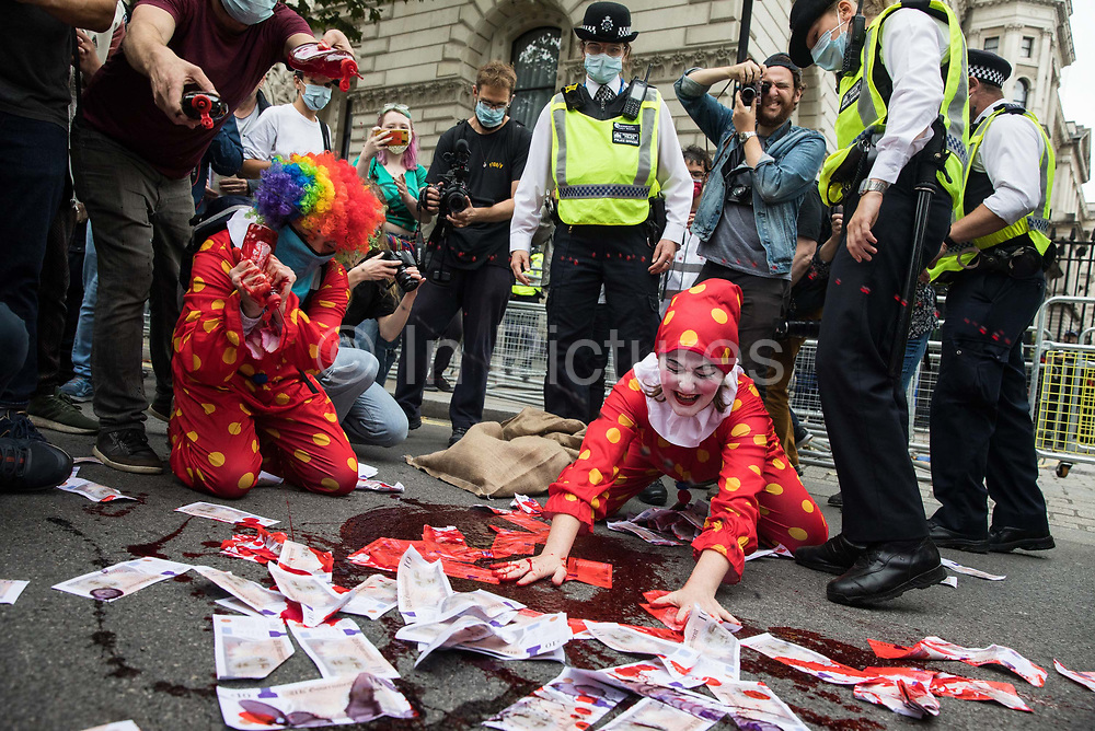 Two clowns spread fake blood and banknotes in the road in front of Downing Street during a 'Carnival of Corruption' protest by climate activists from Extinction Rebellion against the government's facilitation and funding of the fossil fuel industry on 3 September 2020 in London, United Kingdom. Extinction Rebellion activists are attending a series of September Rebellion protests around the UK to call on politicians to back the Climate and Ecological Emergency Bill CEE Bill which requires, among other measures, a serious plan to deal with the UK's share of emissions and to halt critical rises in global temperatures and for ordinary people to be involved in future environmental planning by means of a Citizens' Assembly.