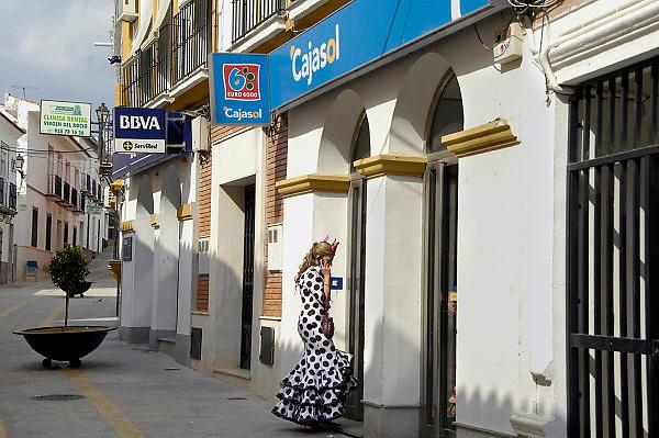 Spanje, Sanlucar, 7-5-2010Een vrouw in flamenco jurk staat bij een pinautomaat, geldautomaat, om geld te pinnen. In Spanje gaat het slecht met de economie en het financiele systeem. 20% werkeloosheid en spaarbanken die in de problemen zijn gekomen. Men wil niet met Griekenland vergeleken worden, maar de tekenen voorspellen niet veel goeds.Posters which call for a demonstration against unemployment and the policies of the government. In Spain the economy and financial system is in bad shape. 20% Unemployment and savings banks that have come into trouble. They do not want to be compared with Greece, but the signs do not predict much good.Foto: Flip Franssen/Hollandse Hoogte