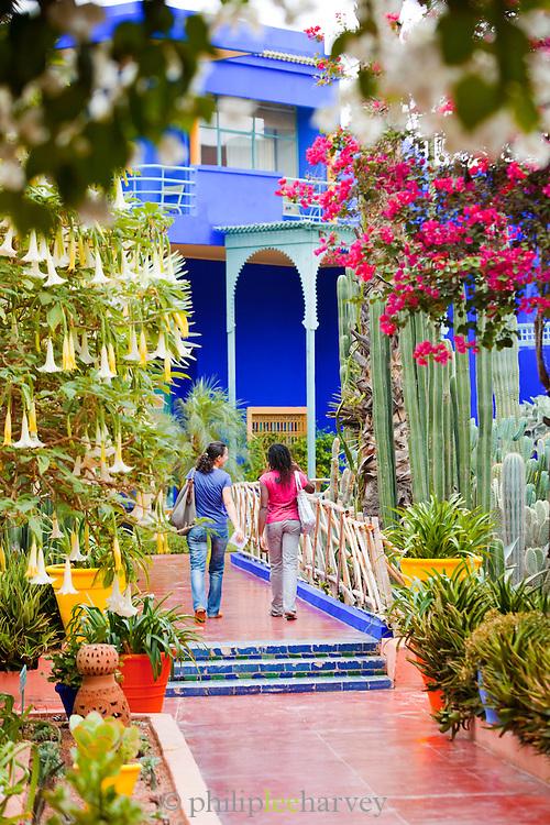 Women walk through the Jardin Majorelle, exotic gardens in Marrakech, Morocco