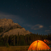 A camper enters his tent below the stars and Cascade Mountain in Banff National Park, Alberta, Canada.