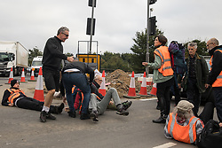 Enfield, UK. 15th September, 2021. Angry motorists move Insulate Britain climate activists blocking a slip road from the M25 at Junction 25 as part of a campaign intended to push the UK government to make significant legislative change to start lowering emissions. The activists, who wrote to Prime Minister Boris Johnson on 13th August, are demanding that the government immediately promises both to fully fund and ensure the insulation of all social housing in Britain by 2025 and to produce within four months a legally binding national plan to fully fund and ensure the full low-energy and low-carbon whole-house retrofit, with no externalised costs, of all homes in Britain by 2030 as part of a just transition to full decarbonisation of all parts of society and the economy.