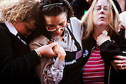 """15 JANUARY 2010 - TUCSON, AZ:    Safeway employees SARAH PREWITT-CHO (left), DAWN GALLAGHER (center, dark hair) and SHAYNE SPUDE (right) comfort each other at the memorial for the victims of a a mass shooting in Tucson, AZ, Saturday, January 15, one week after the shooting. Six people were killed and 14 injured in the shooting spree at a """"Congress on Your Corner"""" event hosted by Arizona Congresswoman Gabrielle Giffords at a Safeway grocery store in north Tucson on January 8. Congresswoman Giffords, the intended target of the attack, was shot in the head and seriously injured in the attack but is recovering. Doctors announced that they removed her breathing tube Saturday, one week after the attack. The alleged gunman, Jared Lee Loughner, was wrestled to the ground by bystanders when he stopped shooting to reload the Glock 19 semi-automatic pistol. Loughner is currently in federal custody at a medium security prison near Phoenix.    PHOTO BY JACK KURTZ"""