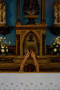 A woman touches the altar after the service at the Catholic church, Cubatao