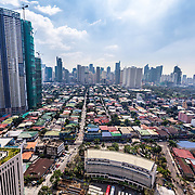 CAPTION: A view of Makati City. In the background is the central business district of Metro Manila and in the foreground, to the right, is a lower-income, flood-prone community living close to the river. Currently, when it floods, many of those settled here are reluctant to evacuate, preferring to remain in their homes to protect their belongings from opportunistic thieves. The most vulnerable people in these communities are informal settlers, the elderly and young children. Makati City Government has relocated many of those living in flood-prone communities, replacing such settlements with linear parks alongside the river to increase soil absorption. LOCATION: Disaster Risk Reduction and Management Office, Makati, Philippines. INDIVIDUAL(S) PHOTOGRAPHED: N/A.