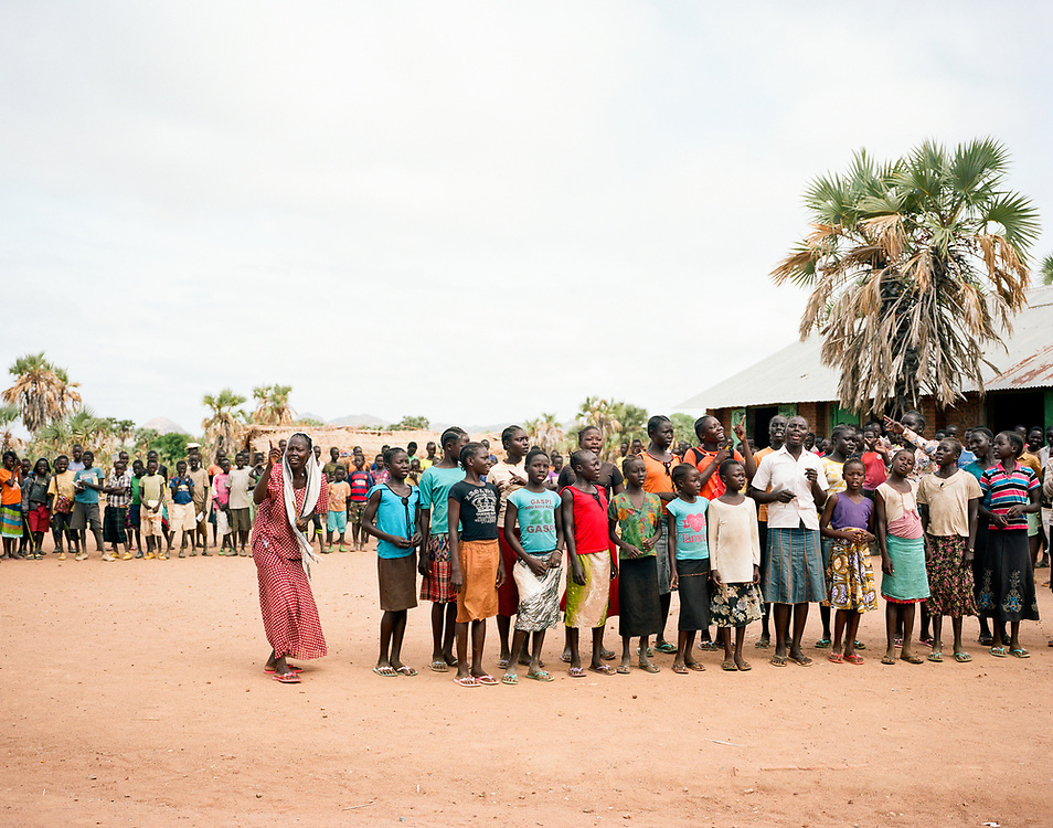 """NUBA MOUNTAINS, SUDAN – JUNE 9, 2018: Schoolteacher Medina Tutu Kafe instructs her choir students at Kororak School. <br /> <br /> In 2011, the government of Sudan expelled all humanitarian groups from the country's Nuba Mountains. Since then, the Antonov aircraft has terrorized the Nuba people, dropping more than 4,080 bombs on hospitals, schools, marketplaces and churches. Today, vestiges of the Antonov riddle the landscapes of daily life, where more than 1 million Nuba live in famine conditions – quietly enduring the humanitarian blockade intended to drive them out of the region. The skies are mostly clear. Yet the collective memory of the bombings remains an open wound, and the Antonov itself a persistent threat. So frequent were the attacks that the Nuba nicknamed the high flying aircraft and its dismal hum: """"Gafal-nia ja,"""" they would declare, running to the hillsides. """"The loss of appetite has come."""""""