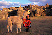 PERU, HIGHLANDS, CUZCO Sacsayhuaman; child and llama