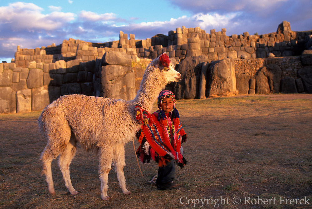 PERU, HIGHLANDS, CUZCO Sacsayhuaman; child and llama