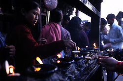 Kathmandu, 13 February 2005. A women lights up a candle to pay respect to Buddha at Swayambhunath Temple