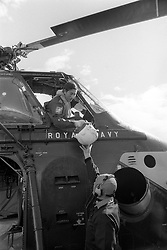 "File photo dated 09/09/74 of Naval Lieutenant the Prince of Wales being handed his flying helmet by a ground crewman before going up for his first ""dual control"" flight with instructor Lieutenant Commander Alan MacGregor in a Royal Navy Wessex V helicopter."