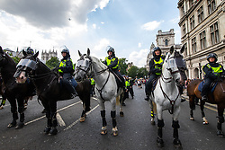 © Licensed to London News Pictures. 14/07/2018. London, UK. Police horses block Westminster Bridge . Supporters of EDL founder Tommy Robinson ( real name Stephen Yaxley-Lennon ) and US President Donald Trump and anti fascists clash on Westminster Bridge during a day of demonstrations and rallies in support and opposed to US President Donald Trump and jailed EDL founder Tommy Robinson . Trump is currently in Scotland and Robinson is in HMP Hull . Photo credit: Joel Goodman/LNP