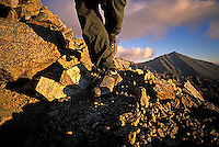 Man hiking at dawn over talus on Split Mountain in the John Muir Wilderness, CA.<br />