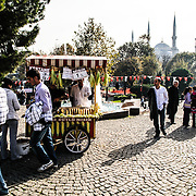 A cart selling grilled corn in a square in Sultanahmet with the Blue Mosque in the background.