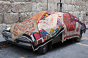 Carpets for sale on a car in Damascus, Syria