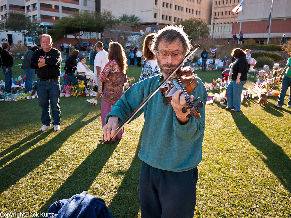 """15 JANUARY 2011 - TUCSON, AZ: MICHAEL SIGLER, from Tucson, plays violin at the memorial on the lawn in front of the University Medical Center in Tucson, AZ, Saturday, January 15. He was playing improvisationally. The memorial has been growing since the mass shooting last week. Six people were killed and 14 injured in the shooting spree at a """"Congress on Your Corner"""" event hosted by Congresswoman Gabrielle Giffords at a Safeway grocery store in north Tucson on January 8. Congresswoman Giffords, the intended target of the attack, was shot in the head and seriously injured in the attack. She is hospitalized at UMC. The alleged gunman, Jared Lee Loughner, was wrestled to the ground by bystanders when he stopped shooting to reload the Glock 19 semi-automatic pistol. Loughner is currently in federal custody at a medium security prison near Phoenix.  PHOTO BY JACK KURTZ"""