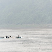 A sampan ferrying people across the Mekong River on a misty morning near Luang Prabang in central Laos.