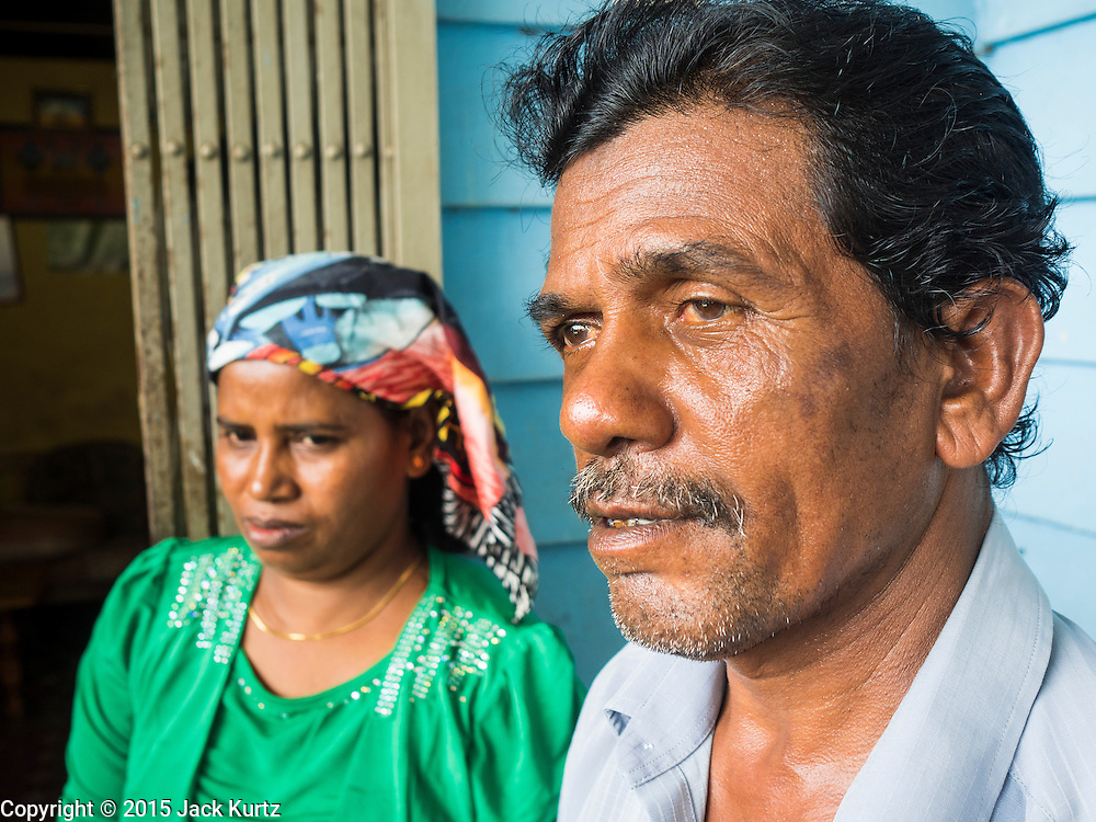 01 JUNE 2015 - KULAI, JOHORE, MALAYSIA:  ZAINAL ABIDIN, a Rohingya refugee in Kulai, Malaysia with his wife. The UN says the Rohingya, a Muslim minority in western Myanmar, are the most persecuted ethnic minority in the world. The government of Myanmar insists the Rohingya are illegal immigrants from Bangladesh and has refused to grant them citizenship. Most of the Rohingya in Myanmar have been confined to Internal Displaced Persons camp in Rakhine state, bordering Bangladesh. Thousands of Rohingya have fled Myanmar and settled in Malaysia. Most fled on small fishing trawlers. There are about 1,500 Rohingya in the town of Kulai, in the Malaysian state of Johore. Only about 500 of them have been granted official refugee status by the UN High Commissioner for Refugees. The rest live under the radar, relying on gifts from their community and taking menial jobs to make ends meet. They face harassment from Malaysian police who, the Rohingya say, extort bribes from them.       PHOTO BY JACK KURTZ