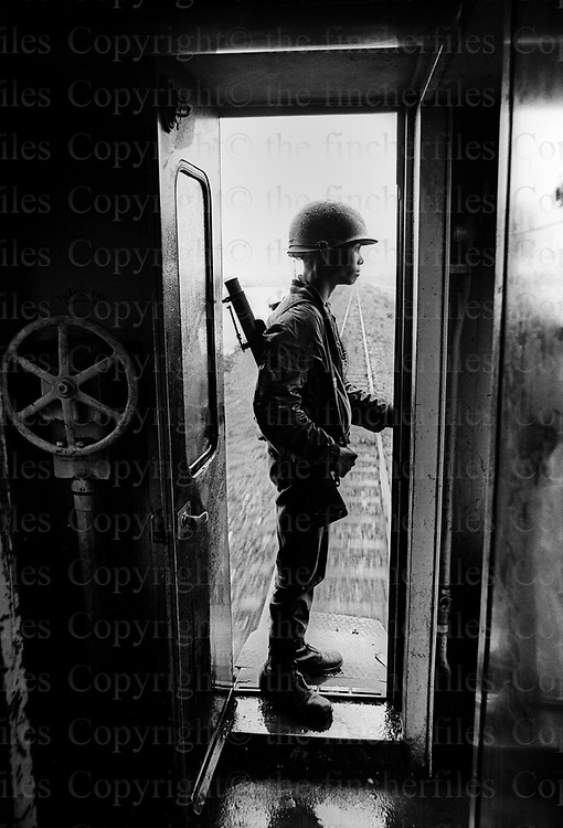A south Vietnamese army soldier stands guard on the train between Hue and Da Nang in Vietnam, September 1969. The Vietnam War was fought between 1st November 1955 until the fall of Saigon on 30 April 1975. Photographed by Terry Fincher.