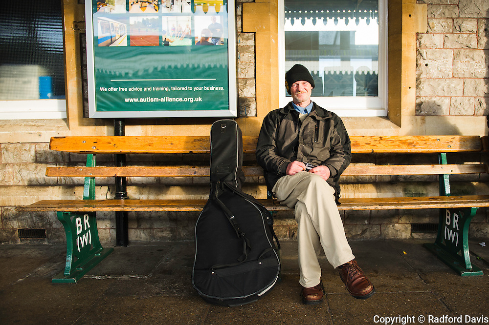 A drifter at the train station in Weston-super-Mare, England, with his guitar.