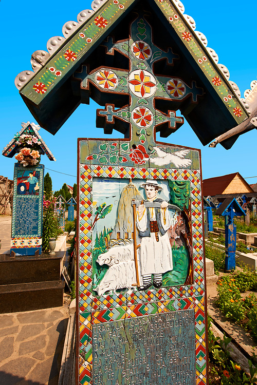 Tombstone of a shepherd , The  Merry Cemetery ( Cimitirul Vesel ),  Săpânţa, Maramares, Northern Transylvania, Romania.  The naive folk art style of the tombstones created by woodcarver  Stan Ioan Pătraş (1909 - 1977) who created in his lifetime over 700 colourfully painted wooden tombstones with small relief portrait carvings of the deceased or with scenes depicting them at work or play or surprisingly showing the violent accident that killed them. Each tombstone has an inscription about the person, sometimes a light hearted  limerick in Romanian. .<br /> <br /> Visit our ROMANIA HISTORIC PLACXES PHOTO COLLECTIONS for more photos to download or buy as wall art prints https://funkystock.photoshelter.com/gallery-collection/Pictures-Images-of-Romania-Photos-of-Romanian-Historic-Landmark-Sites/C00001TITiQwAdS8