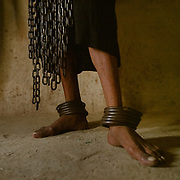"""A """"malang"""", devotee weighing himself down with chains to walk in the heat. In the city of Sehwan Sharif"""