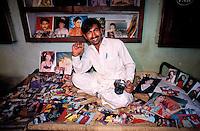 Pakistan - Hijra, les demi-femmes du Pakistan - Mohammed, photographe ne travaille qu'avec les Hijra qui sont d'excellent client. Ici chez lui avec ses tirages //Pakistan. Punjab province. Hijra, the half woman of Pakistan