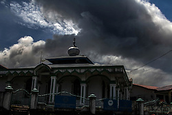 May 25, 2017 - Karo, North Sumatra, Indonesia - A mosque covered as Sinabung volcano spews rolling thick volcanic ash into the air, as seen from Tiga Pancur village on May 25, 2017, North Sumatra province, Indonesia. The activity of Mount Sinabung with the status of Awas (Level IV) increases which volcanic earthquakes have continued to occur with erruptions creating an ash cloud of about 4,000 meters height. Mount Sinabung is one of the most active volcano in Indonesia. (Credit Image: © Ivan Damanik via ZUMA Wire)