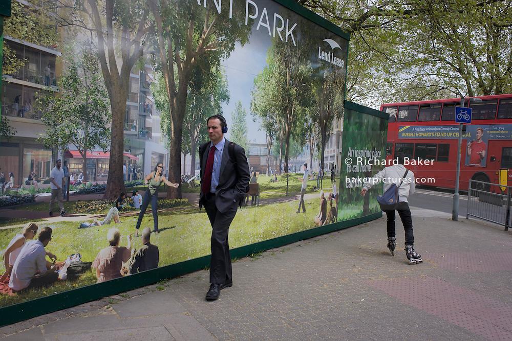South Londoners walk past a regeneration project hoarding image at Elephant & Castle, London borough of Southwark.