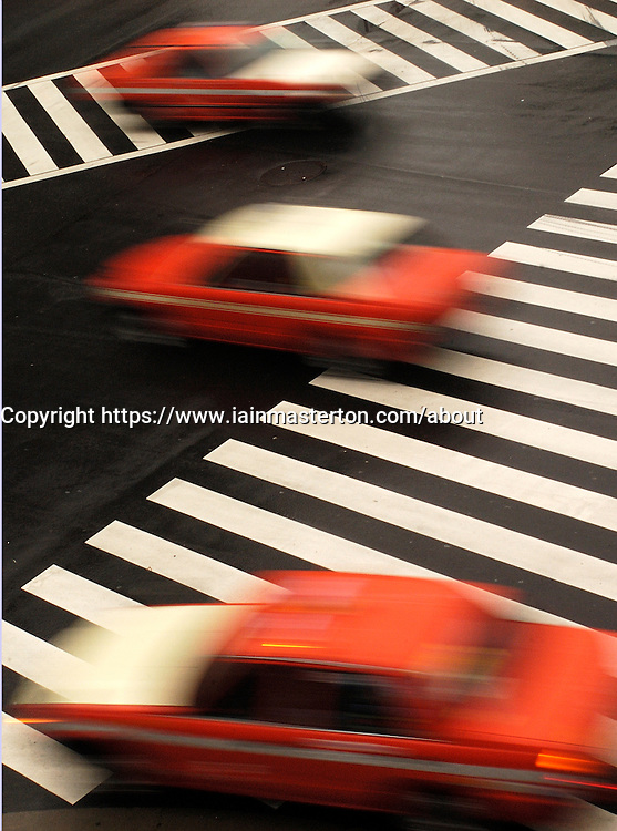 Three red taxis speeding across a street junction in central Tokyo Japan
