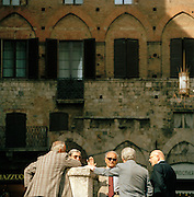 Locals in conversation at the Piazza Del Campo, Siena, Tuscany, Italy