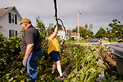 """12 AUGUST 2020 - SLATER, IOWA: SCOTT ALLEY and his wife, DEBBIE ALLEY, clean up debris from trees in their yard that were destroyed by the storm Monday. According to Iowa Governor Kim Reynolds, the storm damaged 10 million acres of corn and soybeans in Iowa, about 1 one-third of Iowa's 32 million acres of agricultural land. Justin Glisan, Iowa's state meteorologist, said the storm Monday, Aug. 10, lasted 14 hours and traveled 770 miles through the Midwest before losing strength in Ohio. The storm was a seldom seen """"derecho"""" that packed straight line winds of nearly 100MPH. The storm pummelled Midwestern states from Nebraska to Ohio.     PHOTO BY JACK KURTZ"""