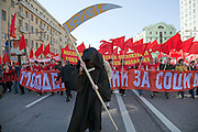 """Moscow, Russia, 01/05/2009..Annual Mayday celebrations in Russia. A demonstrator dressed as the Grim Reaper whose scythe bears the word """"Crisis"""" among several thousand Communist supporters marching through Moscow, with their protests this year focusing on the world economic crisis that has hit the previously booming Russian economy hard."""