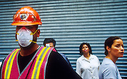 """22 SEPTEMBER 2011 - NEW YORK, NY: A recovery worker wears a dust filter while tourists look at the wreckage of the World Trade Center from a vantage point on Broadway in lower Manhattan near """"Ground Zero"""" of the World Trade Center complex after the WTC terrorist attack, Sept. 22, 2001. More than 2,900 people were killed when terrorists crashed two airliners into the towers on Sept. 11, 2001. The site has turned into a macabre tourist attraction and the crowds are creating problems for law enforcement and recovery workers.   PHOTO BY JACK KURTZ"""