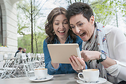 Two friends using digital tablet in the sidewalk cafe, Bavaria, Germany