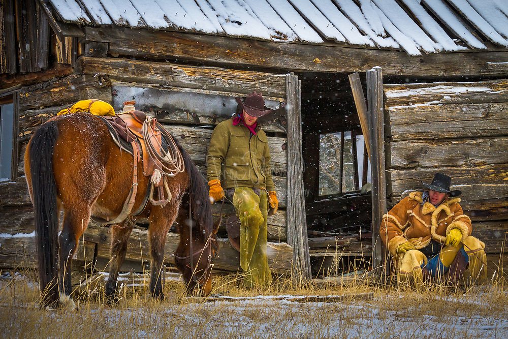 Two cowboys resting at a delipidated cabin in Wyoming