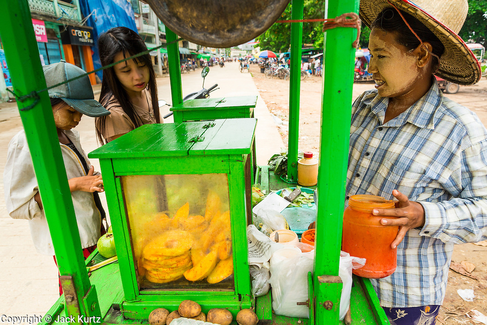 14 JUNE 2013 -  PATHEIN, AYEYARWADY, MYANMAR: A Burmese woman with thanaka powder on her face sells mango from her cart in Pathein, Myanmar. Pathein, sometimes also called Bassein, is a port city and the capital of the Ayeyarwady Region, Burma. It lies on the Pathein River (Bassein), which is a western branch of the Irrawaddy River. It's the fourth largest city in Myanmar (Burma) about 190 km west of Yangon.    PHOTO BY JACK KURTZ