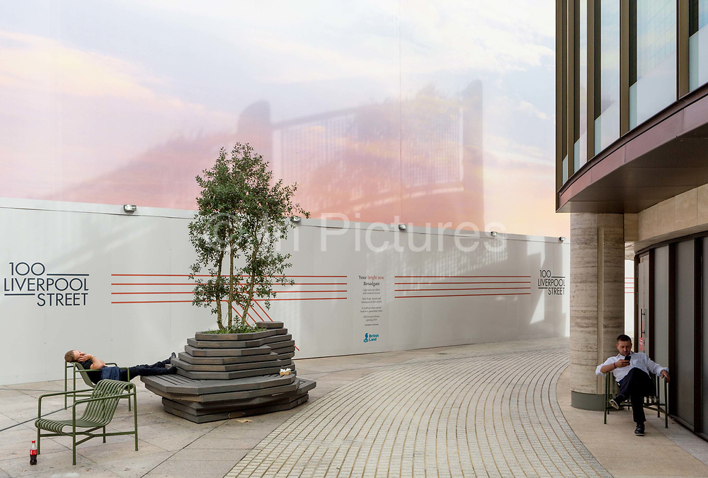 A sleeping man enjoys a moment of quiet solitude below a large construction hoarding, the site of a new office delvelopment for UBS at Broadgate, on 17th Juy 2017, in the City of London, England.