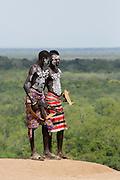 Young male Karo tribe boys with AK-47 rifle . Omo Valley, Ethiopia