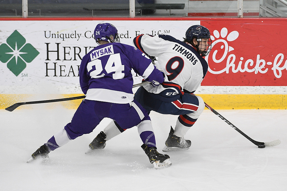 PITTSBURGH, PA - MARCH 13: Jordan Timmons #9 of the Robert Morris Colonials controls the puck against Josef Mysak #24 of the Niagara Purple Eagles in the first period during Game Two of the Atlantic Hockey Quarterfinal series at Clearview Arena on March 13, 2021 in Pittsburgh, Pennsylvania. (Photo by Justin Berl/Robert Morris Athletics)