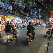 A bustling street in Hanoi's Old Quarter at night, with scooters dashing by and storefonts extending out to the curb.