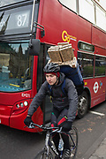 A cyclist carrying boxed flowers pedals past a London bus in the capital, on 4th December 2018, in London England.