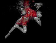 An underwater photo of model with long dark hair in a red dress.