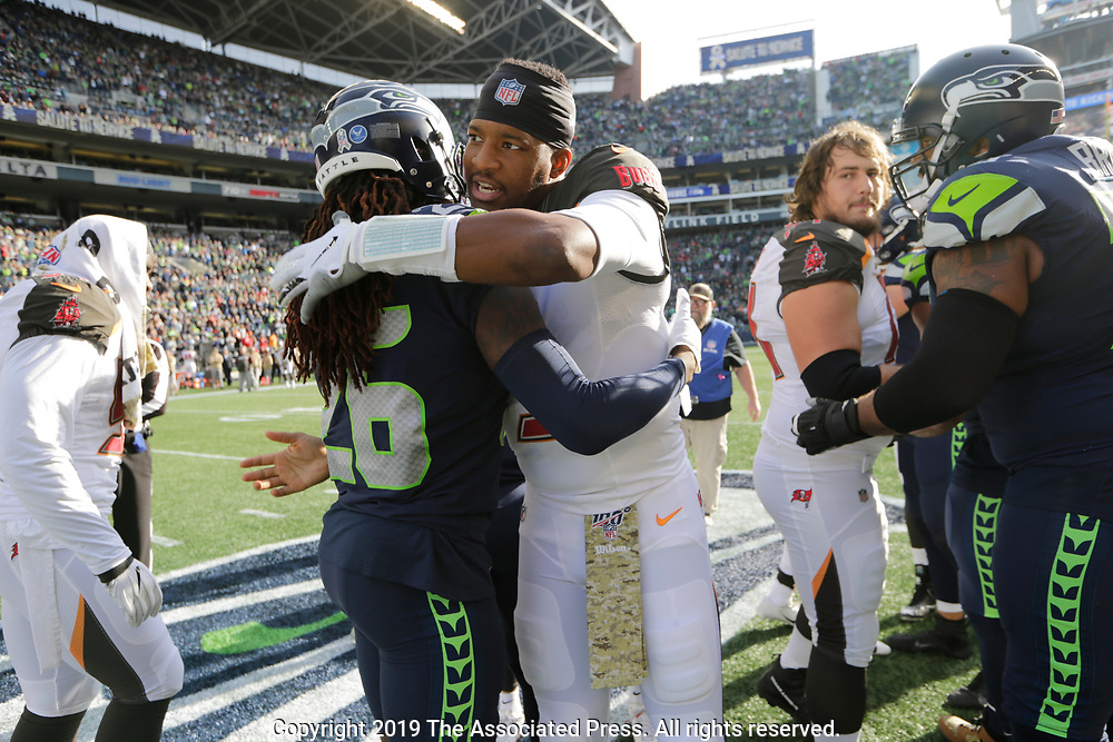 Tampa Bay Buccaneers quarterback Jameis Winston, center, hugs Seattle Seahawks cornerback Shaquill Griffin (26) before the coin toss at the start of an NFL football game, Sunday, Nov. 3, 2019, in Seattle. (AP Photo/John Froschauer)